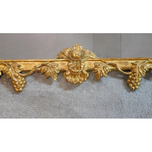 187 - An Florentine style carved giltwood pier mirror with allover fruit and leaf decoration. 150x92cm...