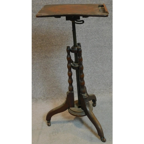 31 - A mid Victorian burr walnut adjustable and articulated music stand on bobbin turned tripod supports....