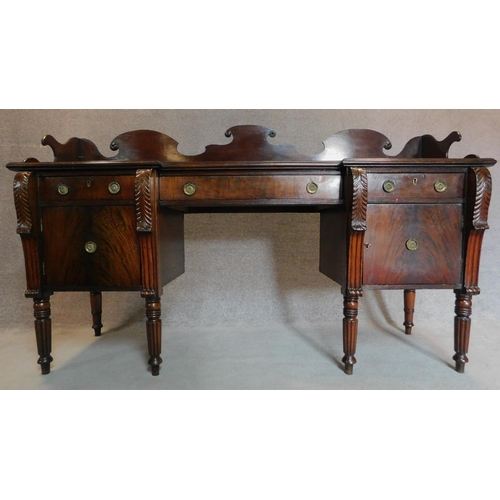 16 - A Regency mahogany sideboard fitted frieze drawers and pair of cupboard doors on spiral tapering ree...