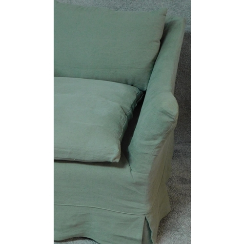 70 - An expansive sofa with large single squab cushion and scatter cushions all feather filled in a sage ...