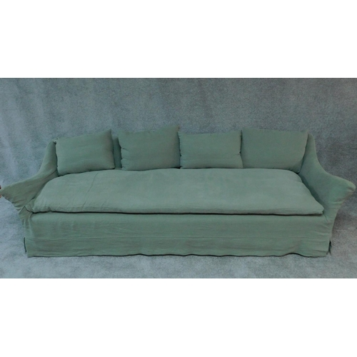 71 - An expansive sofa with large single squab cushion and scatter cushions all feather filled in a sage ...