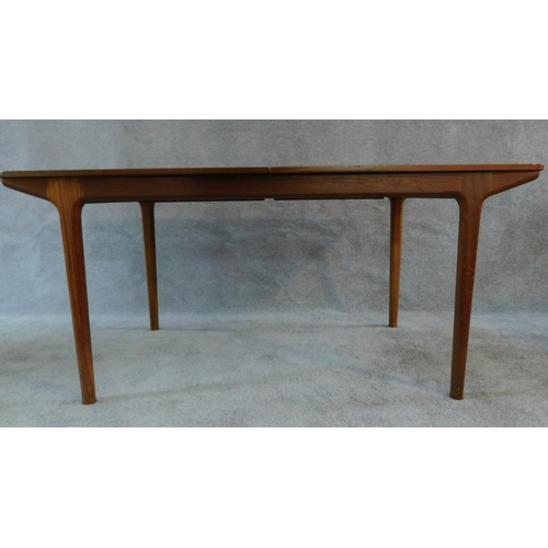 74 - A mid 20th century teak extending dining table with patent action leaves, by McIntosh, makers label ...