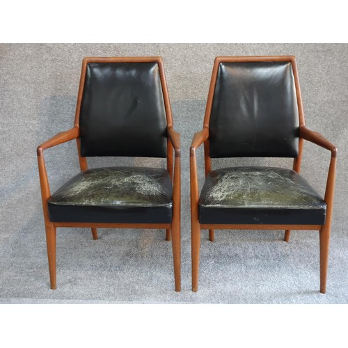 83 - A pair of mid 20th century Danish teak open armchairs in deep green leather upholstery. H.97...
