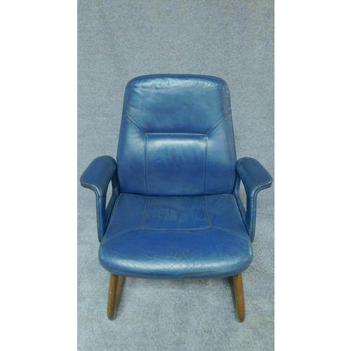 84 - A mid 20th century blue leather upholstered armchair on laminated cantilever base. H.98cm...