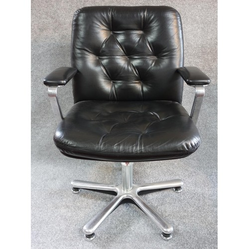 91 - A black leather buttoned back swivel armchair on chrome base. H.91...