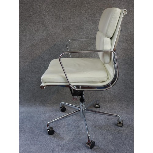 92 - An Eames style swivel armchair in cream leather upholstery. H.96...