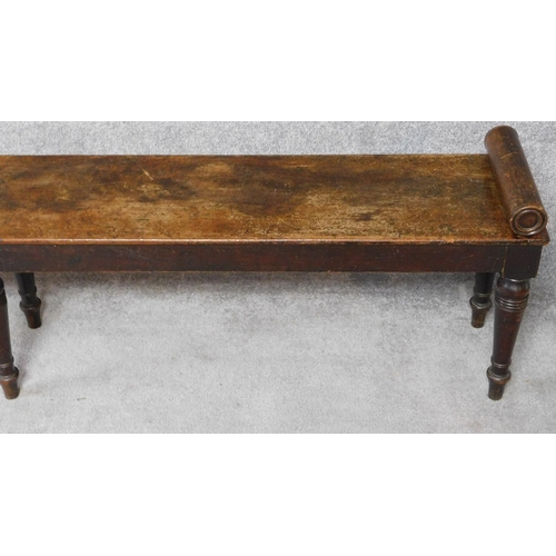 85 - A Regency mahogany long window seat with scroll baton ends on turned tapering supports. H.51 W.215 D...