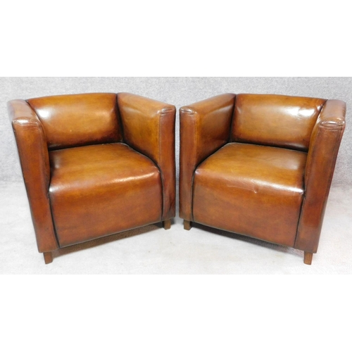 138 - A pair of tan leather club armchairs on square supports. H.74 W.76 D.72cm...