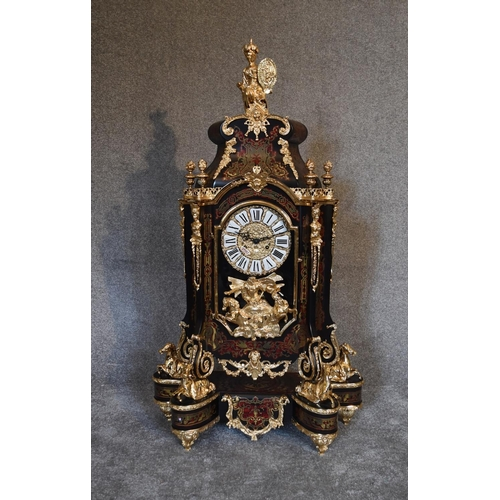 36 - A decorative French style mantel clock in the Boulle manner with  figural surmount on matching eboni...
