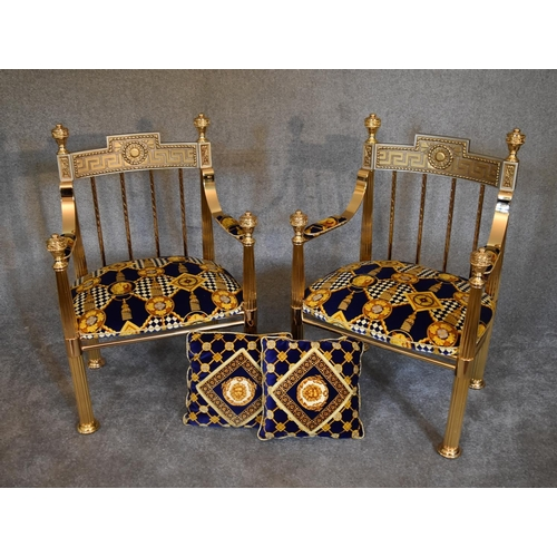 116 - A pair of heavy brass framed Versace style armchairs with greek key pattern back rails and upholster...