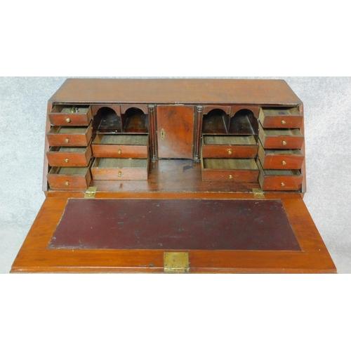 11 - A Georgian mahogany bureau with secret compartment inside fitted interior above four long graduating...