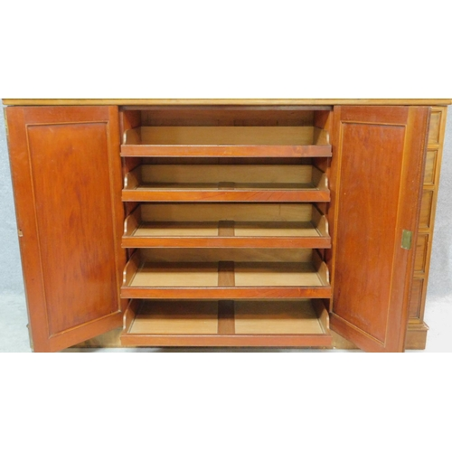 53 - A Regency mahogany press cupboard with fitted central panel doors enclosing linen slides, flanked by...