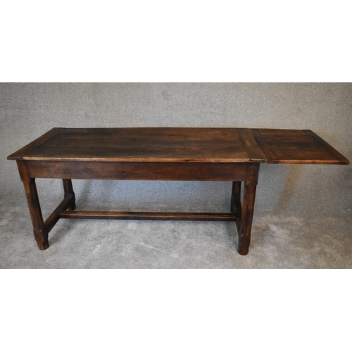 9 - An antique oak farmhouse refectory table with extension leaf to one end and single drawer to the oth...