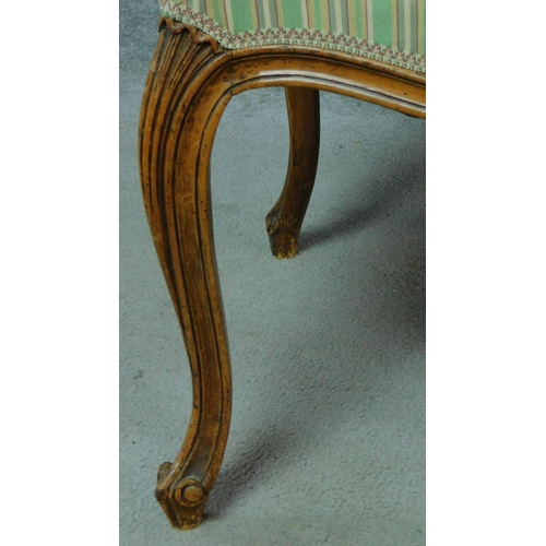 14 - A Victorian walnut armchair with floral carved details and green striped upholstery, raised on cabri...