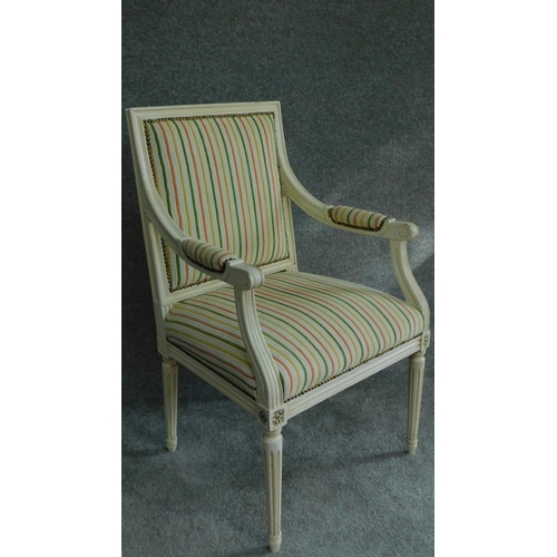 46 - A Louis XVl style painted white armchair in striped upholstery and raised on tapering fluted support...
