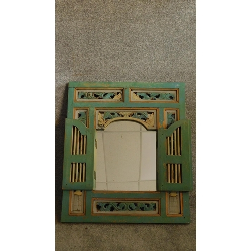 22 - A 19th Century Javanese decorative wall mounted mirror with doors and carved floral together with a ...