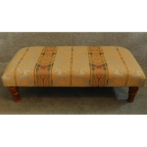 50 - A 20th Century floral upholstered stool raised on tapering turned supports. H.26 W.91 D.46cm...