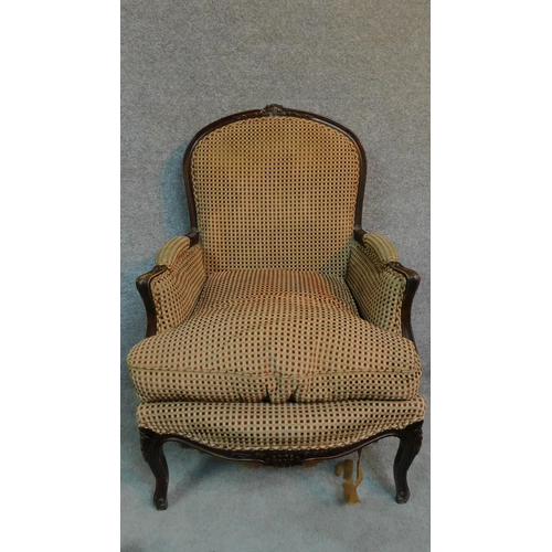 57 - An oak framed Louis XV style armchair with floral carving and red and gold cheque upholstery, raised...