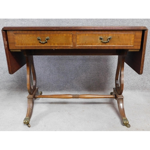 60 - A Regency style mahogany drop flap sofa table with two dummy drawers opposing a pair of drawers. Rai...