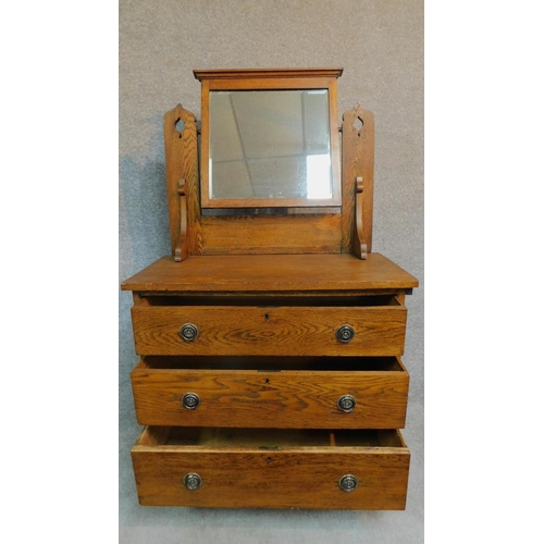 11 - A late 19th century oak three drawer dressing chest with leaf carving and raised on bracket supports...