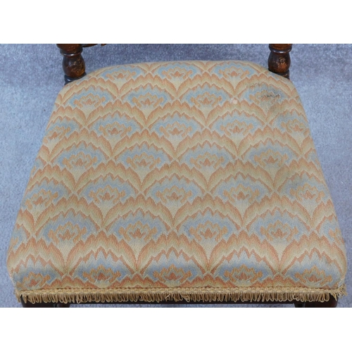 12 - A Victorian oak chair with floral carving to the back and woven peacock feather design upholstery ra...