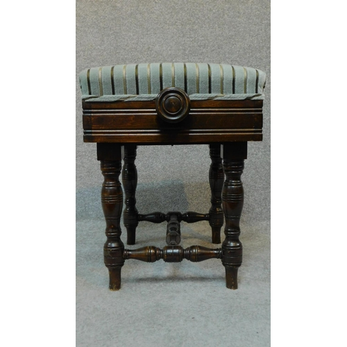 43 - An Edwardian mahogany adjustable piano stool raised on stretchered turned tapering supports. H.46 W....