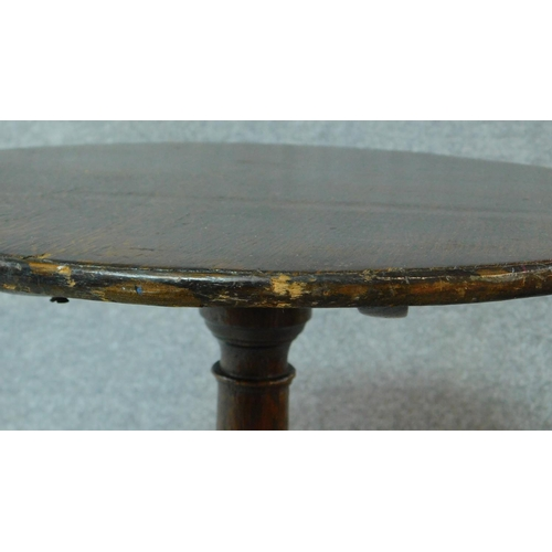 2 - An antique country oak tilt top circular tea table raised on tripod supports. H.67 W.47cm...