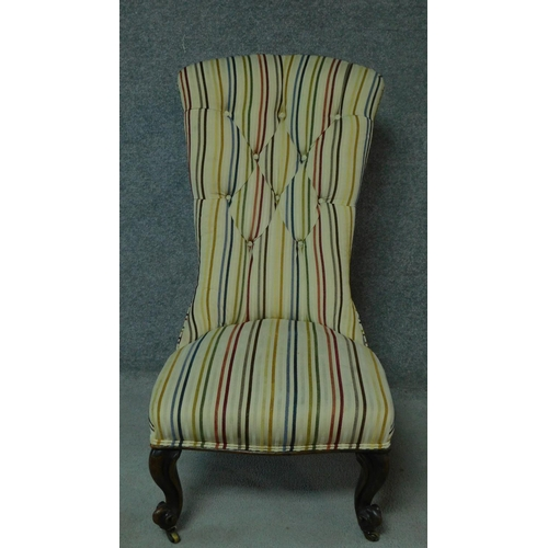18 - A Victorian mahogany nursing chair in candy striped buttoned back upholstery. H.103cm...