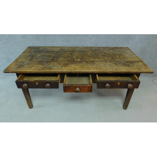 23 - A 19th century oak refectory dining table with three frieze drawers raised on square tapering suppor...