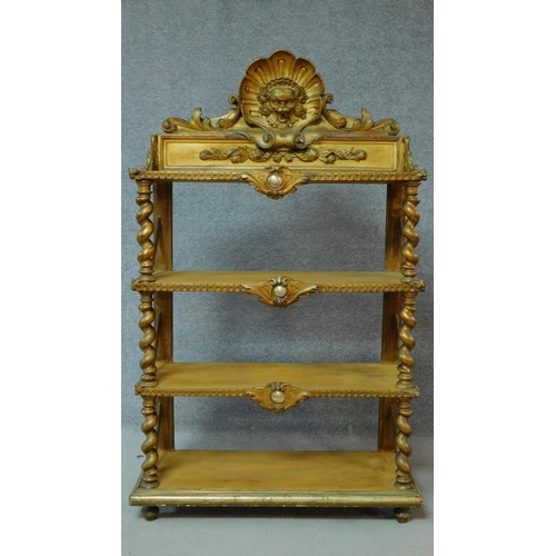 24 - A Victorian carved giltwood whatnot with shell and lion mask carving on barley twist supports. H.136...