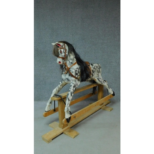 57 - A vintage carved piebald rocking horse with lift off top section. H.115 W.156cm...