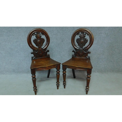 27 - A pair of Victorian oak hall chairs with carved floral shield backs, raised on tapering turned suppo...