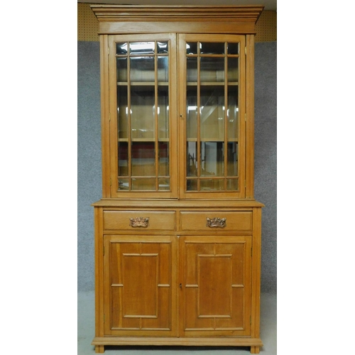 29 - A late Victorian oak library bookcase with glazed upper section, pair of frieze drawers and panelled...