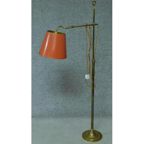 220 - A vintage brass adjustable floor lamp on pedestal base. H.138cm...