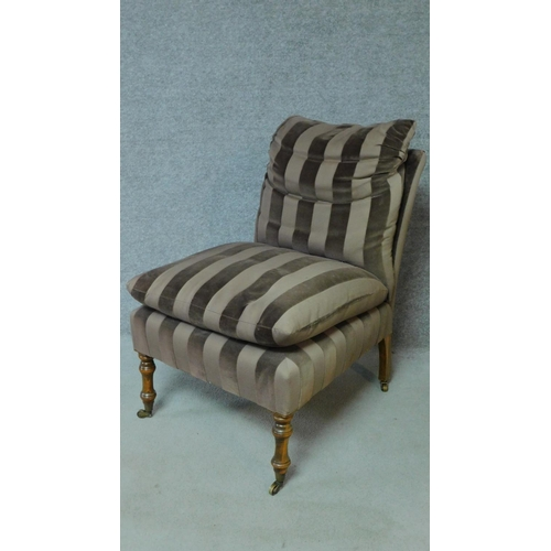 19 - A 19th century style nursing chair in striped upholstery on turned tapering supports. H.87cm...