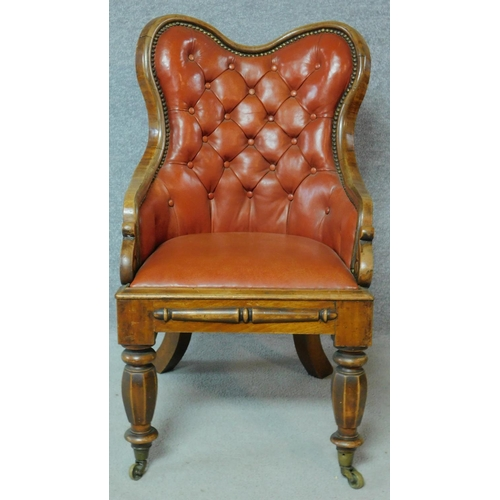 38 - A William IV mahogany framed buttoned back library chair in tan leather upholstery on facetted bulbo...