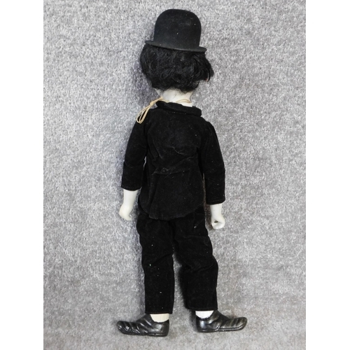 30 - A vintage porcelain Charlie Chaplain doll.  Depicting the Little Tramp with a painted porcelain head...