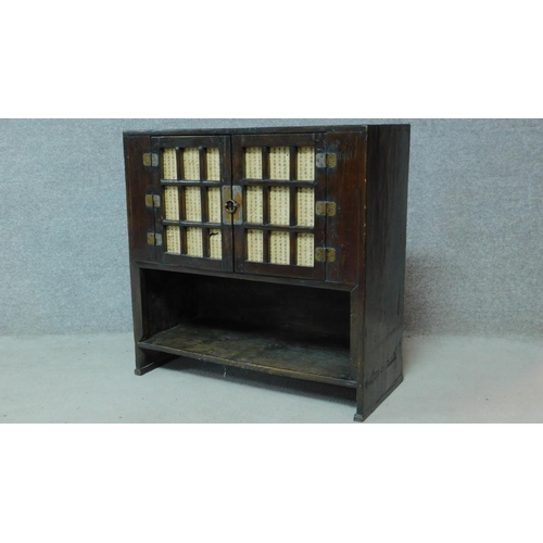 38 - A Chinese hardwood cabinet with panel doors above open compartment. H.71 W.78 D.34cm...