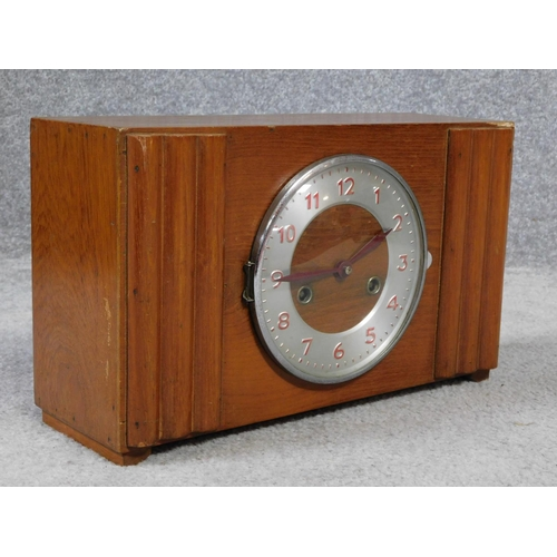 41 - A vibtage oak and metal mantle clock. Red painted numerals.  H.22 W.37 D.13cm...