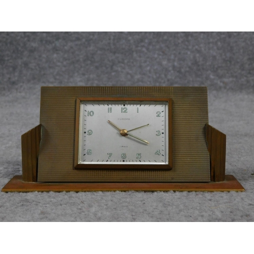 42 - An Art Deco brass desk clock by Europa. Luminous numbers. Geometric form with linear detailing. H.8 ...