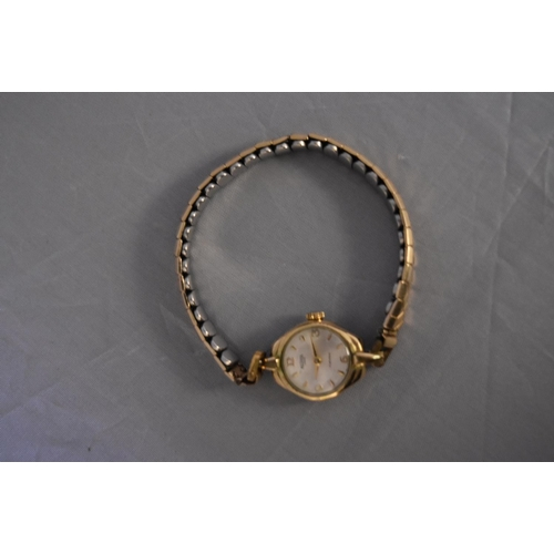 44 - A vintage ladies gold plated hand wound Medana watch. White enamel dial with gold plated markers, on...