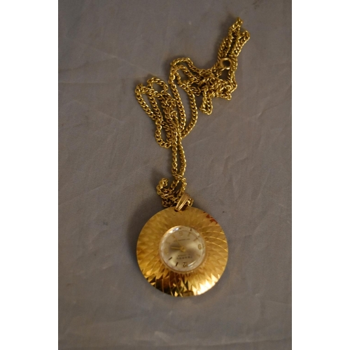 45 - A vintage Tegrov gold tone pendant antimagnetic watch and chain. Impressed floral design to the back...