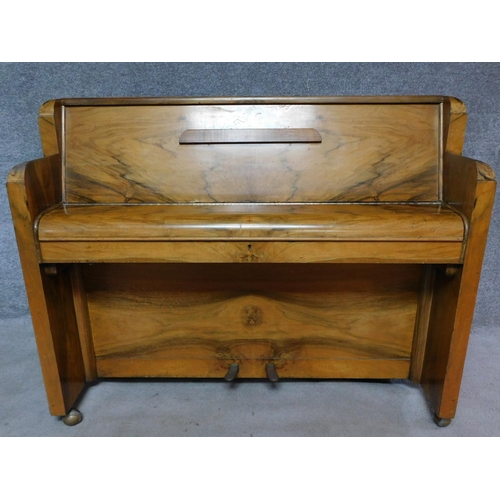 51 - An Art Deco figured walnut upright piano, by Nathaniel Berry & Sons. H.106 W.133 D.48cm...