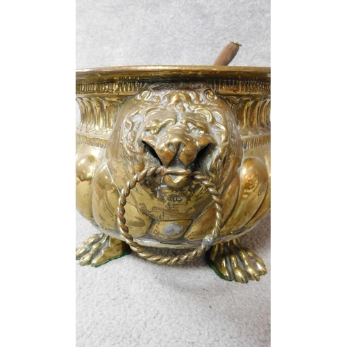 47 - A Victorian repousse brass coal bucket on four lion paw feet and with lion head handles either end. ...