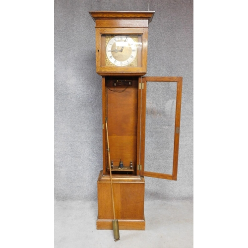 39 - An oak cased grandfather clock, with gilded repousse detailing to the face. Black roman numerals to ...