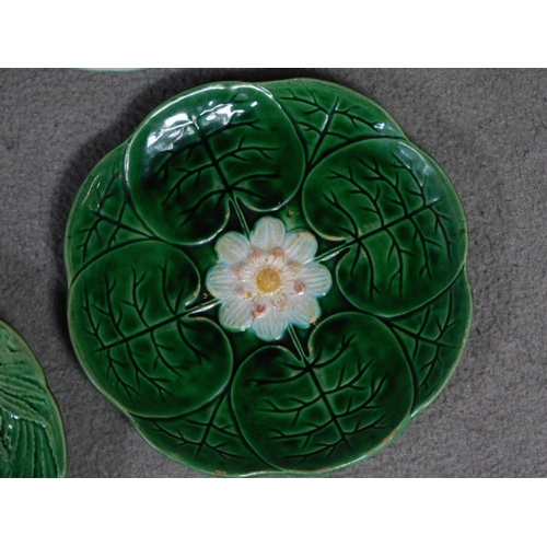 14 - Four antique majolica plates. One designed by George Jones of pineapples in a basket, the waterlilly...