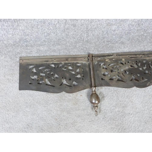 77 - Antique pierced hinged steel and engraved fender. With dragon and urn motifs and two tapering finial...