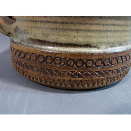 19 - a studio pottery lidded pot and ramakin holder. The lidded two handled pot has an impressed cross an...