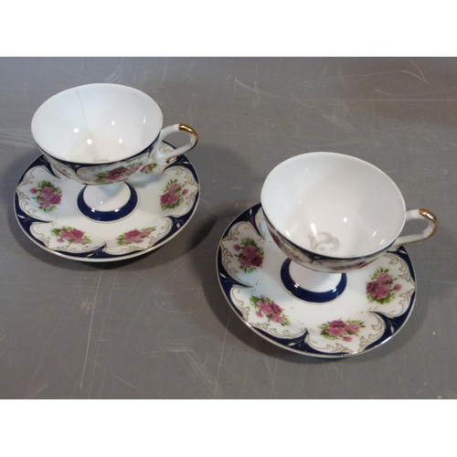 22 - A ceramic Malaysian tea set and a pair of porcelain tea cups and saucers. The tea cups have a printe...