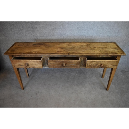 38 - An antique country elm sideboard fitted with three frieze drawers on square tapering supports. H.80x...